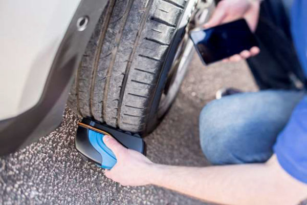 Handheld TreadReader in use on tyre showing mobile app